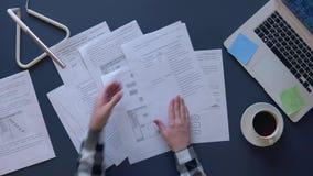 Бизнес-леди в серой рубашке разбирает рабочие планы сидя на таблице и кофе напитков На таблице компьтер-книжка акции видеоматериалы