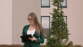 Бизнес-леди в стеклах и деловом костюме пишет что-то в документах акции видеоматериалы