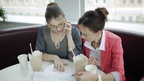 2 бизнес-леди говоря на телефоне с боссом во время перерыв на ланч сток-видео