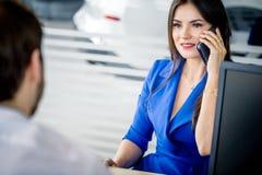 Бизнес-леди говоря на smartphone на автосалоне стоковое изображение