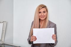 Бизнес-леди держа лист бумаги и смотря камеру Стоковая Фотография RF