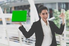 Бизнес-леди держа пустую компьтер-книжку для онлайн дела m стоковая фотография