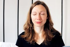 Бизнес-леди Дзэн делая дышая тренировки на кровати ослабила в представлении лотоса стоковое изображение