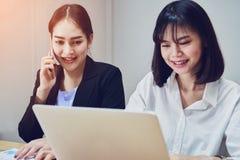 Бизнес-леди используют компьтер-книжки и smartphones для работы в офисе Стоковое Изображение RF