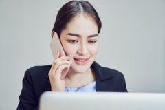 Бизнес-леди используют компьтер-книжки и smartphones для работы в офисе Аутсорсинг обслуживания клиента Стоковая Фотография