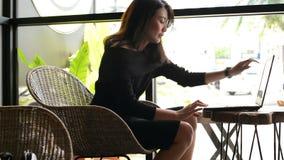 Бизнес-леди используя ноутбук для работы на кафе видеоматериал