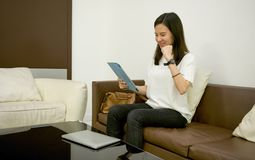Бизнес-леди используя таблетку в живущей комнате на ноче Стоковое Изображение