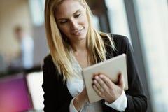 Бизнес-леди используя таблетку в современном офисе Стоковая Фотография RF