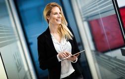 Бизнес-леди используя таблетку в современном офисе Стоковые Изображения