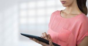 Бизнес-леди используя таблетку против белизны запачкала предпосылку Стоковые Изображения