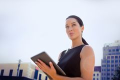 Бизнес-леди используя таблетку против предпосылки города Стоковое фото RF