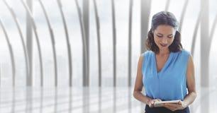 Бизнес-леди используя таблетку против предпосылки здания Стоковые Изображения