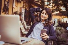 Бизнес-леди используя умный телефон к слушая музыке снаружи Стоковое Изображение RF