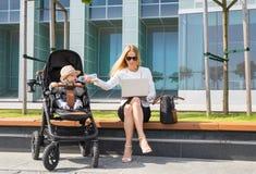 Бизнес-леди и мать работая на компьтер-книжке с младенцем в прогулочной коляске Стоковое фото RF