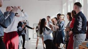 Бизнес-леди менеджера счастливой потехи молодая испанская делая эпичный танец с многонациональной командой на ЭПОПЕЕ замедленного видеоматериал
