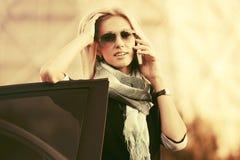 Бизнес-леди моды в солнечных очках вызывая на сотовом телефоне стоковая фотография