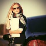Бизнес-леди моды в солнечных очках рядом с ее автомобилем стоковое изображение