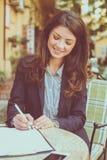 Бизнес-леди на документах сочинительства кафа Стоковая Фотография RF