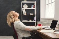 Бизнес-леди отдыхая в офисе, выпивая кофе Стоковые Фотографии RF