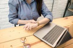 Бизнес-леди печатая на клавиатуре и наблюдая на его наручных часах Принципиальная схема контроля времени стоковое изображение rf