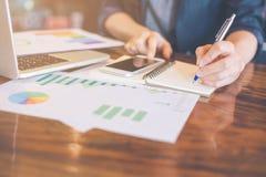 Бизнес-леди пишет журналы анализа о диаграммах и диаграммах стоковое изображение