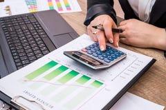 Бизнес-леди показывая финансовые диаграммы с компьтер-книжкой Стоковые Фотографии RF