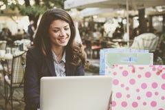 Бизнес-леди после ходя по магазинам серфинга на интернете, на кафе, usin Стоковое Фото