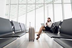 Бизнес-леди по ее умному телефону ждать в аэропорте стоковое фото rf