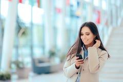 Бизнес-леди проверяя телефон в офисном здании стоковая фотография rf