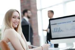 Бизнес-леди работая в офисе с диаграммой дела на компьютере Стоковое фото RF