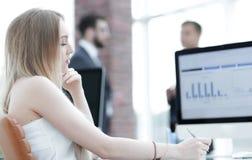 Бизнес-леди работая в офисе с диаграммой дела на компьютере Стоковая Фотография RF