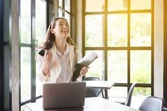 Бизнес-леди работая в офисе с документами Счастливый победитель праздновать бизнес-леди успеха кричащий стоковая фотография