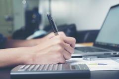 Бизнес-леди работая на ее столе офиса с документами и компьтер-книжкой Коммерсантка работая на бумаге Стоковая Фотография RF