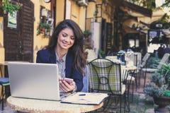 Бизнес-леди работая на кафе на компьтер-книжке используя умный телефон Стоковая Фотография