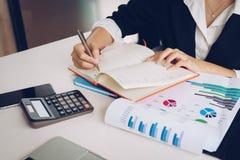 Бизнес-леди работая с финансовыми данными используя калькулятор и стоковое фото rf