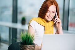 Бизнес-леди сидя в офисе на столе, смотрящ компьтер-книжку и smartphone польз Стоковые Изображения RF