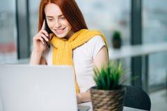 Бизнес-леди сидя в офисе на столе, смотрящ компьтер-книжку и smartphone польз Стоковое Изображение RF