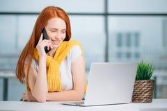 Бизнес-леди сидя в офисе на столе, смотрящ компьтер-книжку и smartphone польз Стоковое Изображение