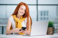 Бизнес-леди сидя в офисе, смотрящ графики и smartphone польз Стоковая Фотография