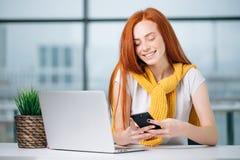 Бизнес-леди сидя в офисе, смотрящ графики и smartphone польз Стоковое Изображение RF