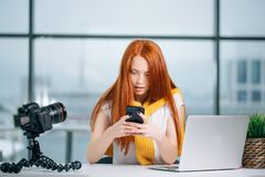 Бизнес-леди сидя в офисе, смотрящ графики и smartphone польз Стоковое фото RF