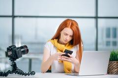 Бизнес-леди сидя в офисе, смотрящ графики и smartphone польз Стоковое Изображение