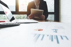Бизнес-леди сидя на офисе и используя com таблетки и компьтер-книжки Стоковые Фото