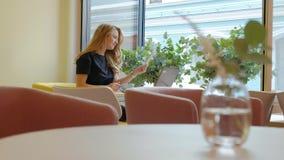 Бизнес-леди сидя на таблице в кофе кафа выпивая и работая на компьтер-книжке сток-видео