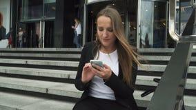 Бизнес-леди сидя на шагах городского здания и используя smartphone видеоматериал