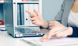2 бизнес-леди сидя совместно и работая на компьтер-книжке Исполнительные власти встречая в лобби офиса Женщина указывая на Стоковая Фотография RF