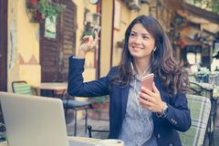 Бизнес-леди снаружи, используя телефон к слушая музыке Стоковые Изображения