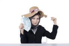 Бизнес-леди счастливого выражения молодая держа банкноту над белой предпосылкой Стоковые Фотографии RF