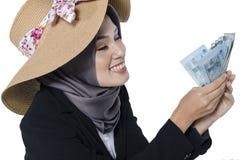 Бизнес-леди счастливого выражения молодая держа банкноту над белой предпосылкой Стоковая Фотография