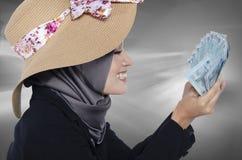 Бизнес-леди счастливого выражения молодая держа банкноту над белой предпосылкой Стоковые Изображения